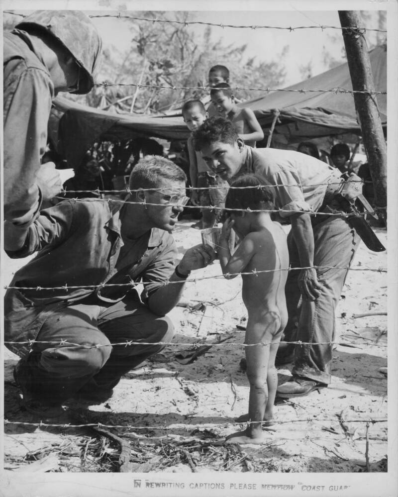 Soldiers Console Naked Child Behind Wire