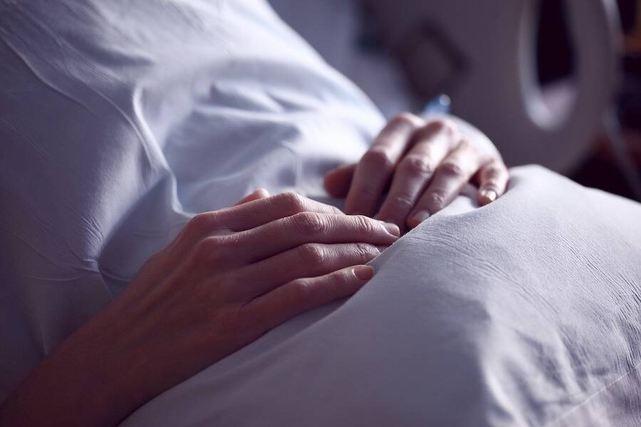 Patient Holding Pillow In Bed
