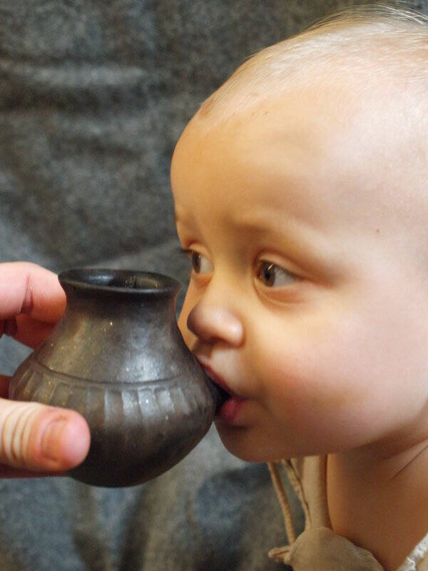 Baby Drinking From Prehistoric Bottle
