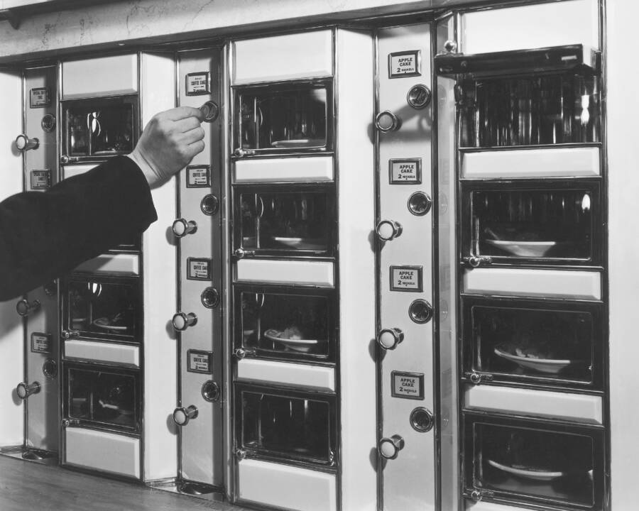 Man Places Coin In Automat