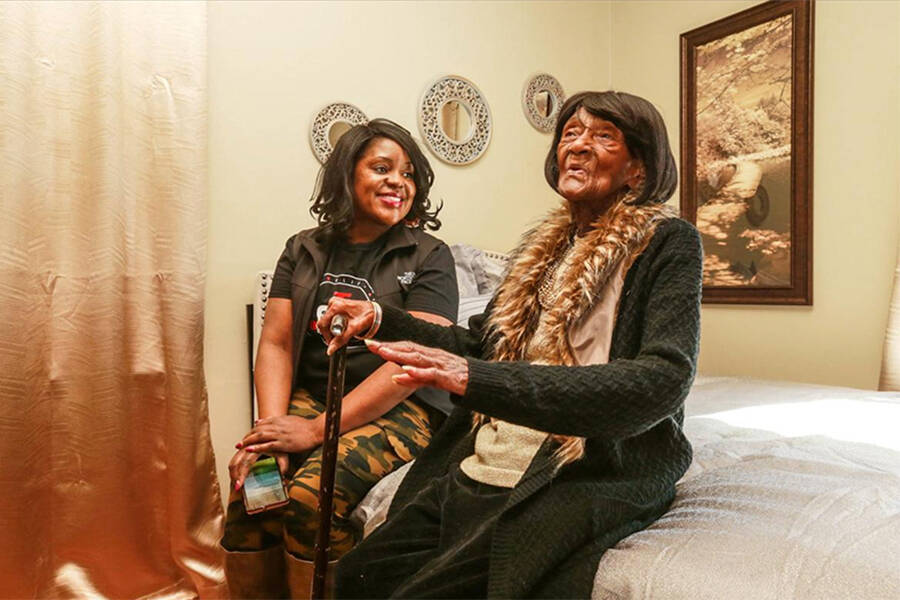 Lessie Randle And Tiffany Crutcher Sit On A Bed In Randles Restored Childhood Home